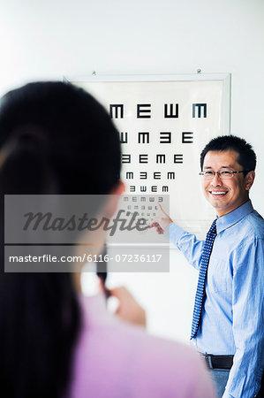 Optometrist administering an eye exam on a eye chart