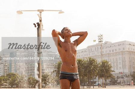 Young man showering on Copacabana Beach, Rio de Janeiro, Brazil