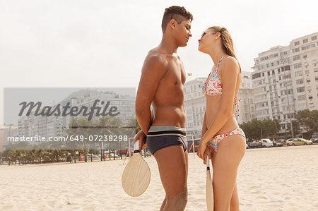 Young couple about to kiss on Copacabana Beach, Rio de Janeiro, Brazil