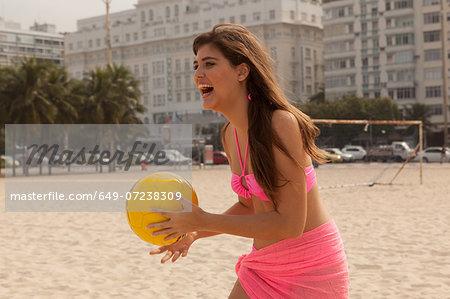 Young woman holding yellow beach ball, Copacabana Beach, Rio De Janeiro, Brazil