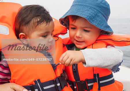 Boy zipping baby's life jacket