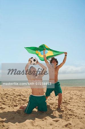 Men holding up brazilian flag on beach