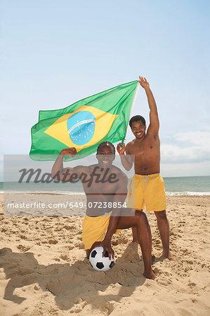 Men posing with brazilian flag on beach