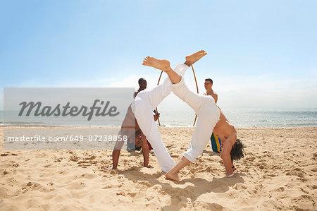 Men doing capoeira on beach