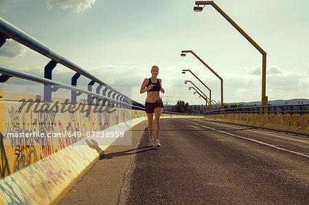Young female jogger running on bridge
