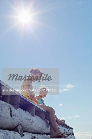 Mother and daughter sitting on pier, Utvalnas, Gavle, Sweden