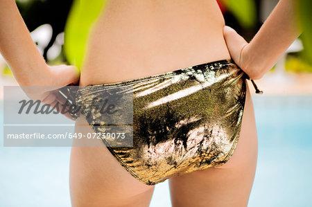 Close up portrait of female buttocks wearing gold bikini bottoms