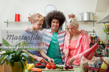 Friends preparing vegetables in kitchen