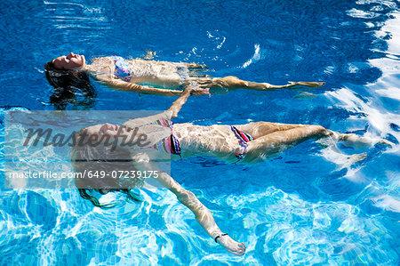 Two teenage girls floating in swimming pool