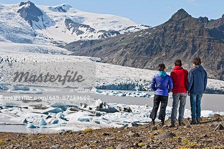 Three people admiring  Fjallsarlon lagoon, Skaftafell, Iceland