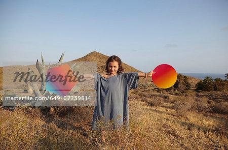 Girl holding bright shapes in desert, Cabo de Gata, Almeria, Spain