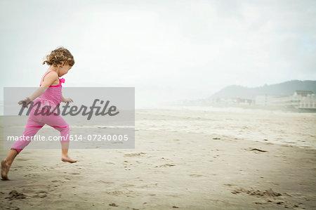 Female toddler running on beach