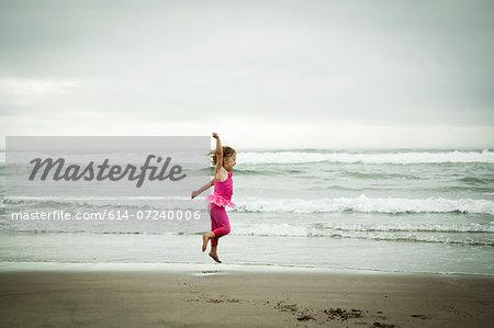 Female toddler jumping on beach