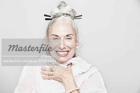 Studio portrait of sophisticated senior woman laughing