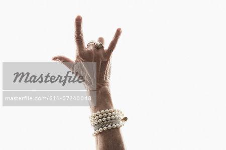 Studio shot of mature woman's hand making gesture