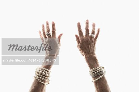Studio shot of mature woman's reaching hands