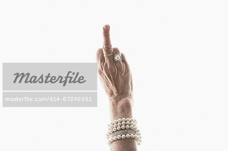 Studio shot of mature woman's hand making obscene gesture