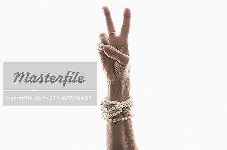 Studio shot of mature woman's hand making peace gesture