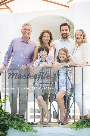Multi-generation family smiling at balcony railing