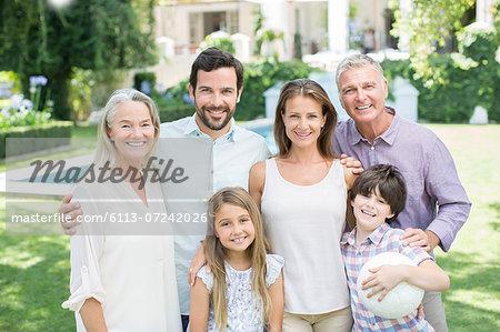 Multi-generation family smiling in backyard