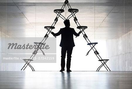 Businessman arranging office chair installation art