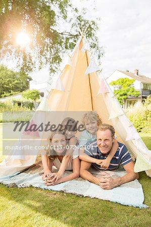 Family relaxing in teepee in backyard