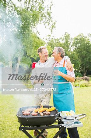 Men hugging at barbecue in backyard