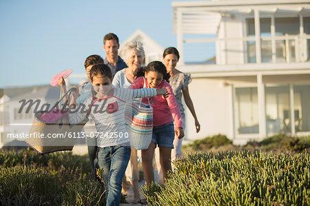 Family walking on beach path outside house