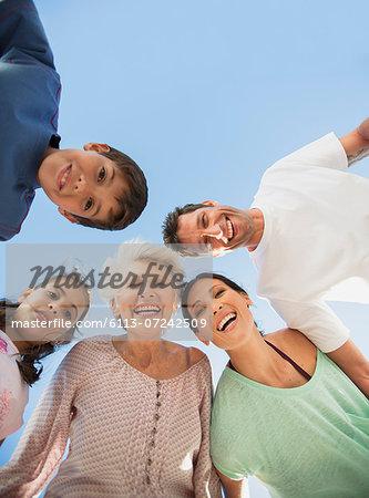 Multi-generation family smiling in huddle against blue sky