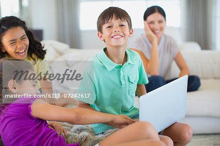 Family using laptop on sofa in living room