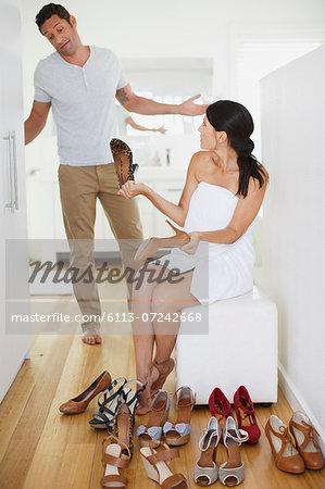 Man helping girlfriend choose shoes in bedroom