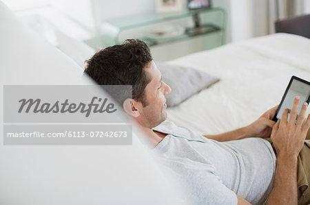 Man using digital tablet on bed