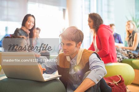 University student using laptop in lounge