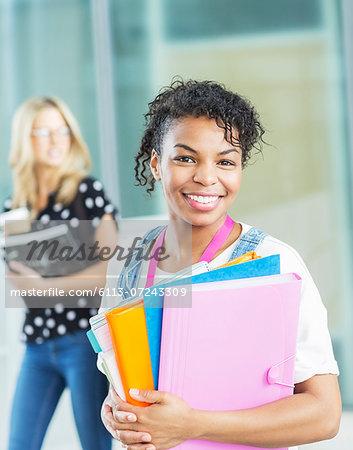 Smiling university student carrying folders