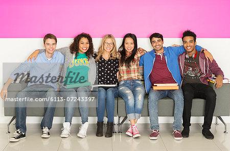 University students smiling on bench
