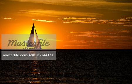 Silhouette of sailboat at sunset on Lake Michigan.