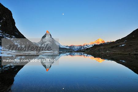 Matterhorn reflected in Lake Riffelsee at Sunrise with Moon, Zermatt, Alps, Valais, Switzerland