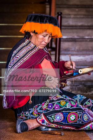 Portrait of Peruvian woman weaving wearing traditional costume, Cusco, Peru