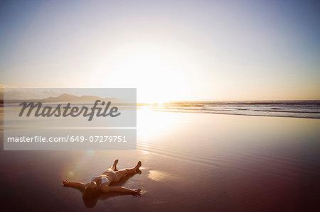 Woman lying on beach, Lanzarote, Canary Islands, Spain