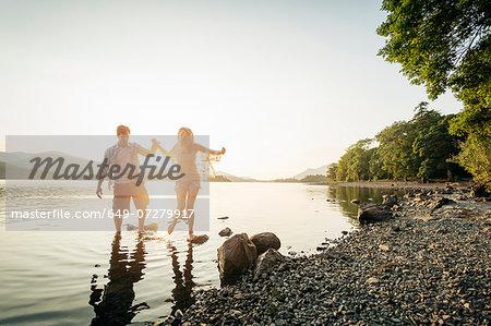 Young couple paddling in lake, Cumbria, England, UK