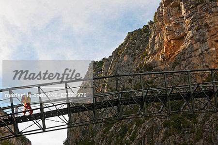 Hiker on hanging footbridge over Verdon Canyon, Provence, France