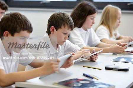 Row of schoolchildren working in class
