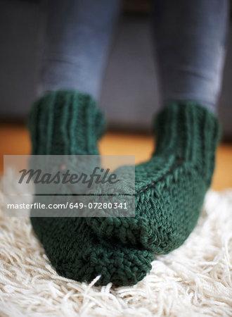 Pair of feet in green knitted socks