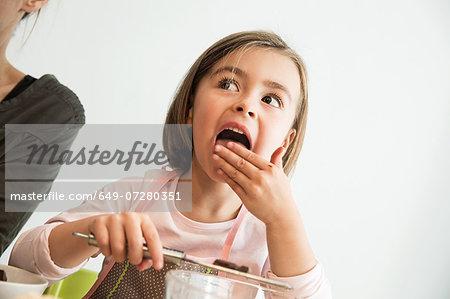 Girl licking batter from fingers