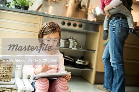 Girl using digital tablet in kitchen