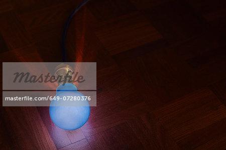 Still life of blue lightbulb on parquet floor