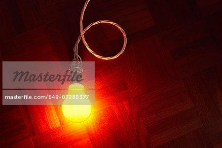 Still life of glowing lightbulb on parquet floor