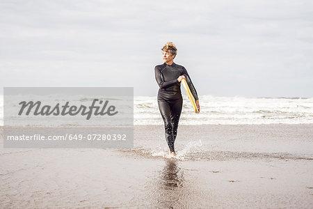 Mature female bodyboarder paddling on Devon coast, UK