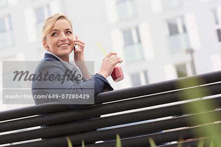 Business woman having lunch break on park bench
