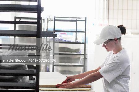 Baker cutting bread dough